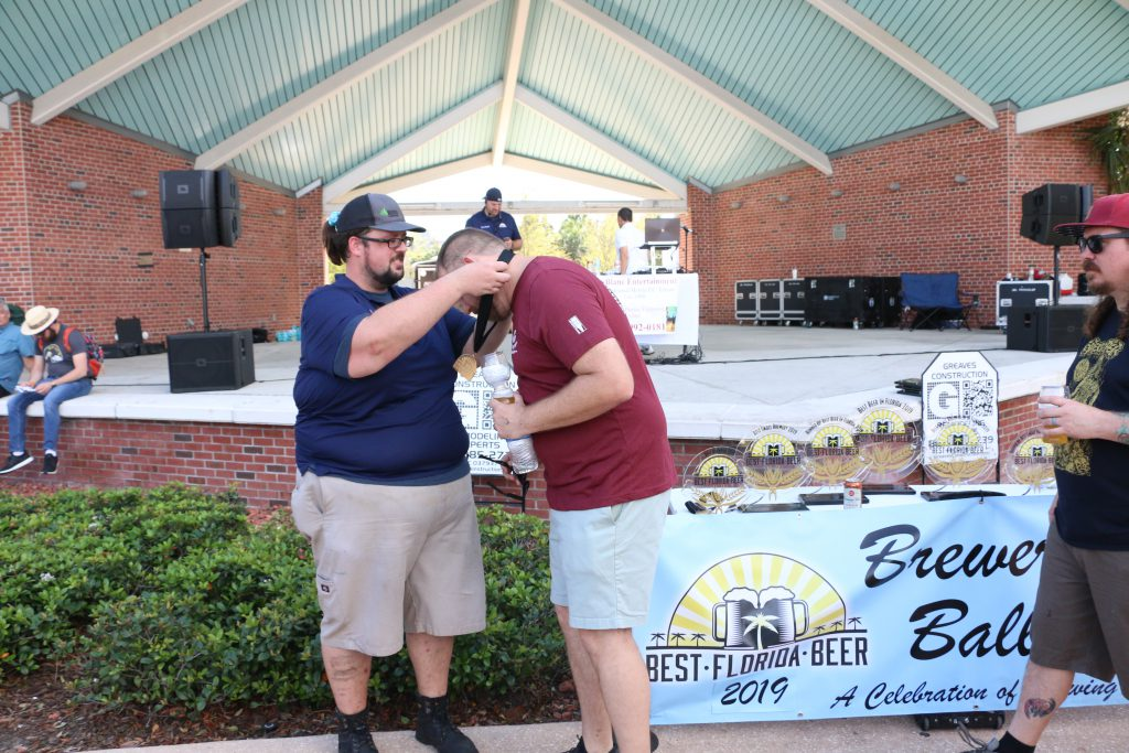 Coppertail Brewing's Casey Hughes accepts a medal at 2019 Brewers Ball Best Florida Beer Competition
