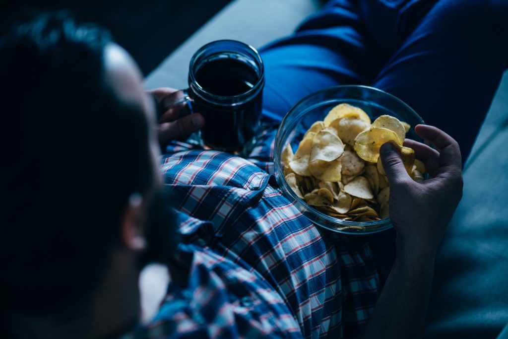 Man eating takeout food and watching movie with a beer