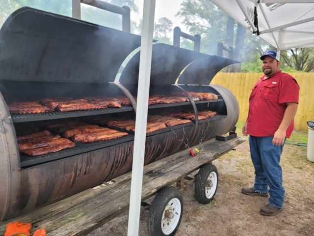 Team Cone Sales Manager Kenny Kinsey watches over ribs and Boston butts as they cook